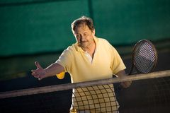Active senior man. In his 70s is offering his hand on the tennis court with tennis racket in other hand. Outdoor, sunlight royalty free stock photography