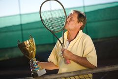 Active senior man. In his 70s is very thankful to his tennis racklet while holding a cup in hand. Outdoor, sunlight Royalty Free Stock Image