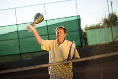 Active senior man. In his 70s is posing on the tennis court with tennis racket in hand. Outdoor, sunlight Stock Photography