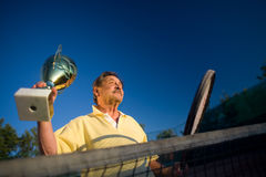 Active senior man. In his 70s is posing on the tennis court with cups in hands. Outdoor, sunlight Royalty Free Stock Photo