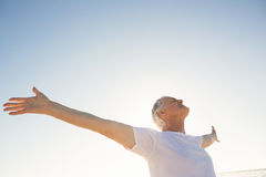 Active senior man with arms outstretched standing against clear sky Royalty Free Stock Images