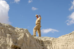 Active Senior Man Beckoning. Senior man beckoning from high up on a cliff with a big blue sky. To view all 4 images from this series keyword: khaki/man Stock Photo