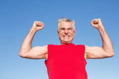 Active senior man cheering in red tank top. On a sunny day stock photography