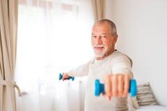 Senior man doing exercise at home. Stock Photo