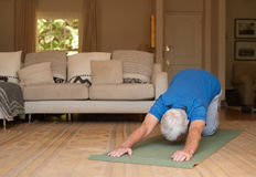 Active senior man exercising on a yoga mat at home. Active senior man doing the child pose while practicing yoga on a matt alone in his living room at home Royalty Free Stock Image