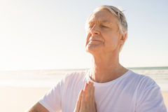 Active senior man with eyes closed in prayer position at beach. On sunny day Royalty Free Stock Photography