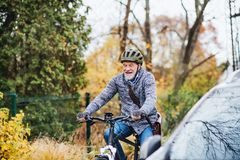 Active senior man with electrobike cycling outdoors in park. royalty free stock image