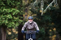 Active senior man with electrobike cycling outdoors on a road in nature. An active senior man with helmet and electrobike cycling outdoors on a road in nature stock photo