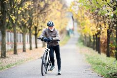 Active senior man with electrobike standing outdoors on a road in nature. royalty free stock photo