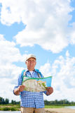 Active Senior Man Hiking in Nature. Portrait of active senior man travelling on hiking trip wearing backpack, looking away holding map Stock Photo