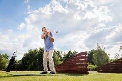 Active senior man hitting a golf ball. Active senior man hitting a golf ball on a golf course Stock Photo
