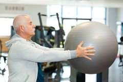 Active senior man holding fitness ball. Active senior man holding a fitness ball Royalty Free Stock Images