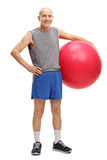 Active senior man holding a fitness ball. Full length portrait of an active senior man holding a pink fitness ball isolated on white background Royalty Free Stock Images