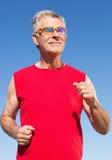 Active senior man jogging on the pier Stock Photos