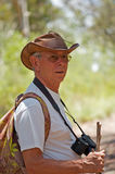 Active senior man outdoors. Candid portrait of handsome active mature man hiking outdoors with a camera and cowboy hat protecting him from the sun on a warm day Stock Images