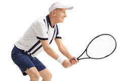 Active senior man playing tennis. Profile shot of an active senior man playing tennis isolated on white background Royalty Free Stock Photography