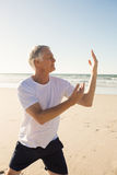 Active senior man practicing yoga. At beach during sunny day Royalty Free Stock Photos