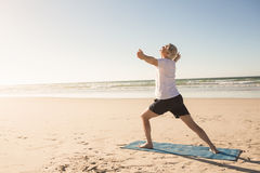 Active senior man practicing yoga at beach. On sunny day stock photography