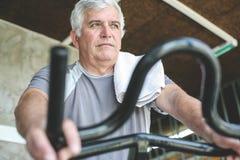 Active senior man sitting on elliptical machine. Workout in gym Stock Photos