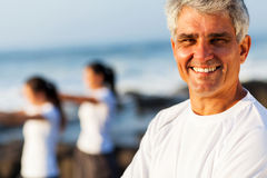 Active senior man. Smiling handsome active senior man posing at the beach with family royalty free stock photos