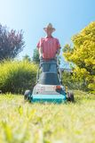 Active senior man smiling while using a grass cutting machine in the garden. Low-angle view of an active senior man smiling and looking at camera while using a royalty free stock photography