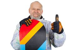 Active senior man with snowboard. Active senior man wearing ski suit holding his snowboard and showing thumbs up on isolated background Royalty Free Stock Photos