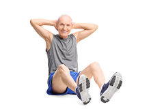 Active senior man in sportswear doing stomach crunches. And looking at the camera isolated on white background Stock Photo