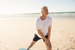 Active senior man stretching at beach. On sunny day Royalty Free Stock Photography