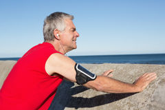 Active senior man stretching before a jog. On a sunny day Stock Image