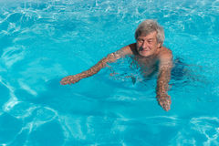 Active senior man swimming. In an outdoor pool on a sunny day Royalty Free Stock Image