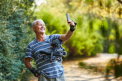 Active senior man taking a selfie. With his inline skates Royalty Free Stock Images