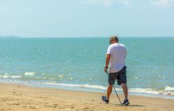 Active senior man walking with nordic walking poles on the beach royalty free stock photography