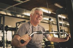 Active senior man working exercise in the gym. Man workout in gym royalty free stock photo