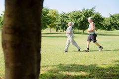 Active senior people jogging in city park. Active retirement, senior couple running and exercising in city park. Copy space royalty free stock images