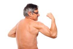 Active senior showing biceps royalty free stock photo