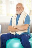 Active senior sitting on fit ball. With arms crossed, smiling at camera Stock Photos