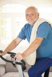 Active senior using exercise bike Royalty Free Stock Photo