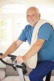 Active senior using exercise bike. At home, smiling at camera royalty free stock photo