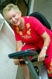 Active senior woman. A senior woman rides on an exercise bike on her patio stock photo