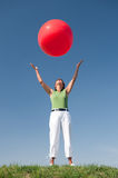 Active senior woman. With a big red ball in front of blue sky stock photo