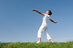 Active senior woman. Is doing some gymnastics in front of blue sky stock images