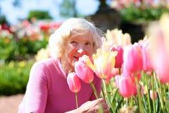 Active senior woman enjoying flowers park Royalty Free Stock Photos