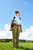 Active Senior Woman Enjoying Hiking Trip. Portrait of active senior woman travelling on hiking trip, posing smiling happily against clear blue sky royalty free stock photos