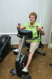 Active Senior Woman Exercise Bike Machine. An active senior woman enjoys her retirement and keeps active by exercising in the retirement community exercise gym Royalty Free Stock Photos