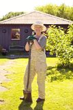 Active senior woman with gardening tools. Full length portrait of active senior woman wearing hat with gardening tools smiling outdoors. Elder woman standing Royalty Free Stock Photography