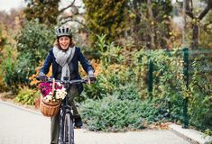 Active senior woman with electrobike cycling outdoors in town. stock photos
