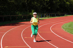 Active senior woman jogging. In a stadium royalty free stock photography