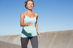 Active senior woman jogging on the pier Stock Image