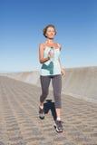 Active senior woman jogging on the pier Stock Photo