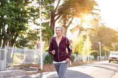 Active senior woman jogging. Smiling senior woman jogging on streets in early morning. Active mature woman running on a sunny day while listening to music. Lady stock photos